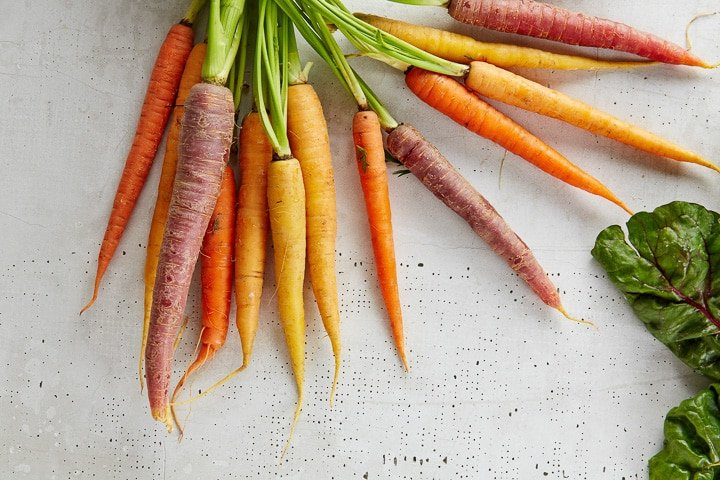 Bunch of mixed colour carrots - yellow, red and orange, with greens attached