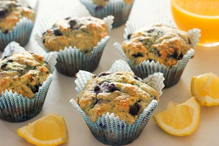 Blueberry lemon muffins with lemon wedges and glass of orange juice