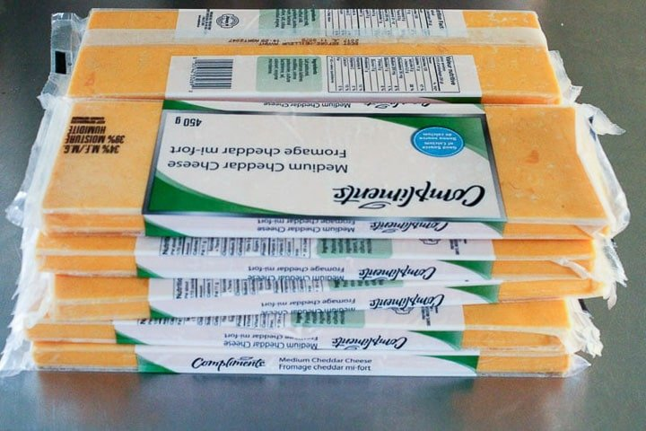 Large packages of cheddar cheese stacked in pile