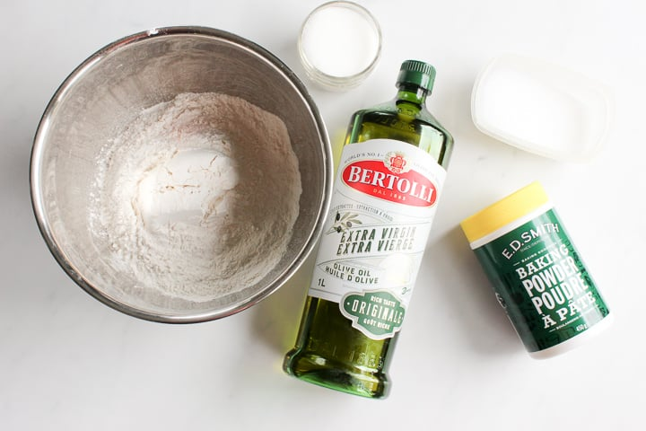 Bowl of flour, bottle of olive oil, baking powder, salt and sugar