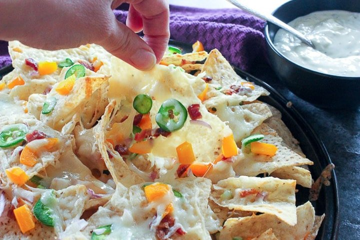 Pan of nachos with jalapeno peppers, bacon and mozzarella cheese