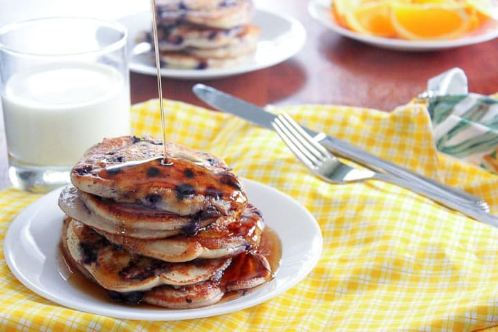 Stack of blueberry pancakes and glass of milk on yellow checkered table cloth