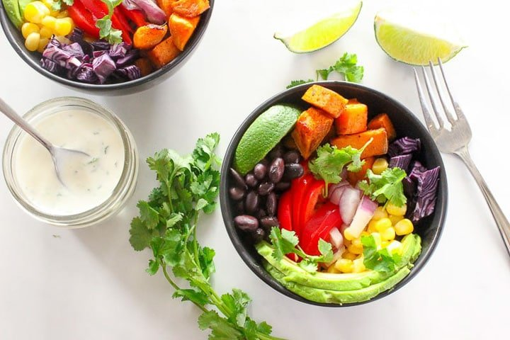 Black bowls piled with roasted sweet potato cubes, black beans, red pepper, avocado, corn, onion, lime and red cabbage, cilantro on side