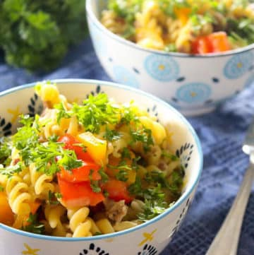 Two bowls of fusilli pasta with peppers and parsley