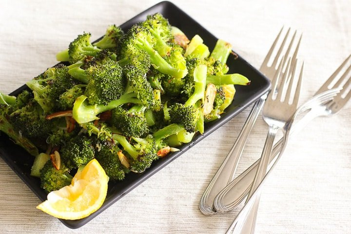 Black plate piled with roasted broccoli and lemon wedge