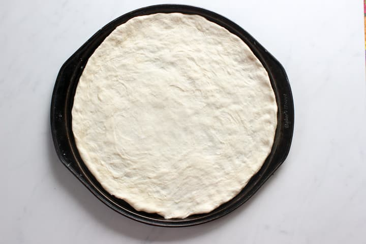 Thin crust pizza dough spread in round pizza pan