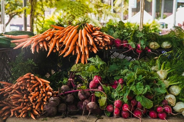 Radishes, carrots and beets at a market stall