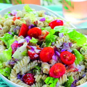 Serving bowl full of bacon, lettuce, tomato pasta salad with creamy sauce