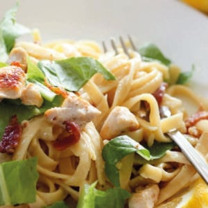 Pasta topped with chicken, bacon and lettuce in white plate.