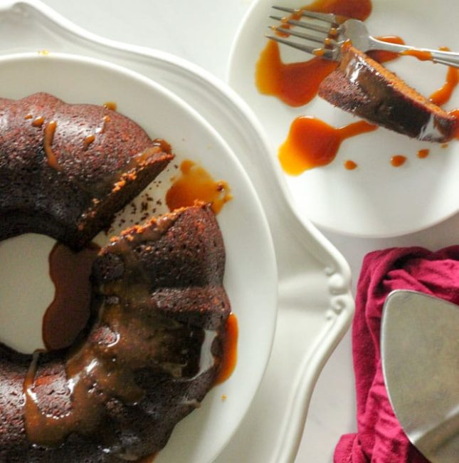 Gingerbread Cake with Caramel Sauce on White Cake Platter.