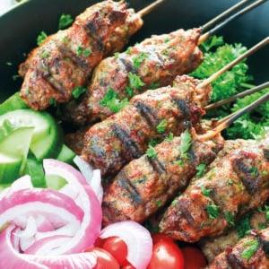 Large bowl of grilled hamburger kebabs and vegetables
