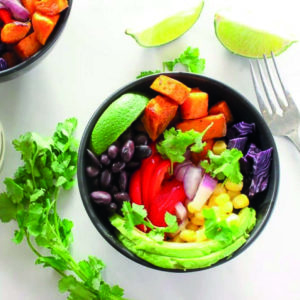 Black bowls piled with roasted sweet potato cubes, black beans, red pepper, avocado, corn, onion, lime and red cabbage, cilantro on side.