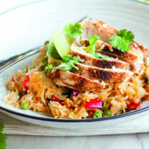Rice topped with sliced chicken and cilantro on white plate.