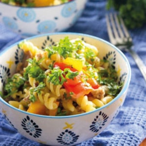 Pasta topped with vegetables and parsley on white bowls.