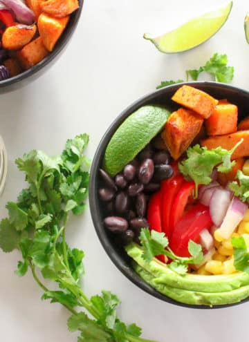 Two black bowls of roasted sweet potato cubes, sliced red peppers and avocados, black beans, corn kernels, cilantro leaves and a lime wedge