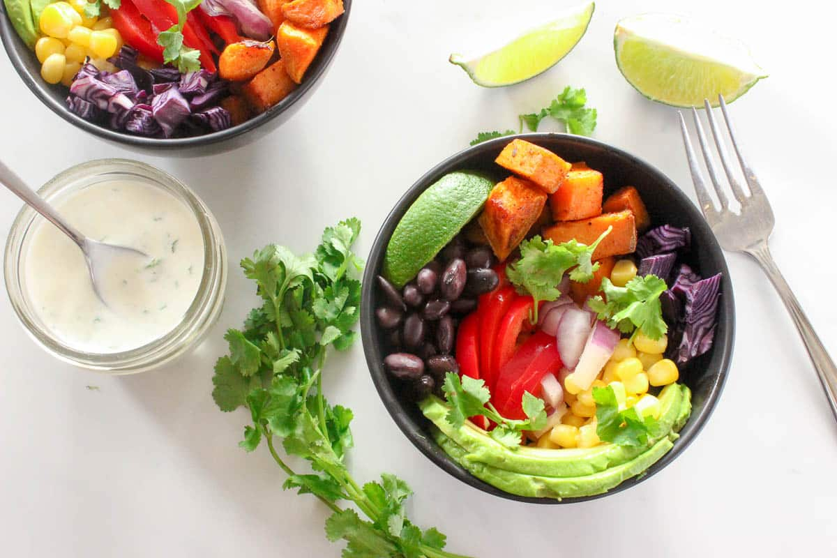 Two black bowls ofsweet potato, red peppers, avocado, black beans, corn, cilantro and lime