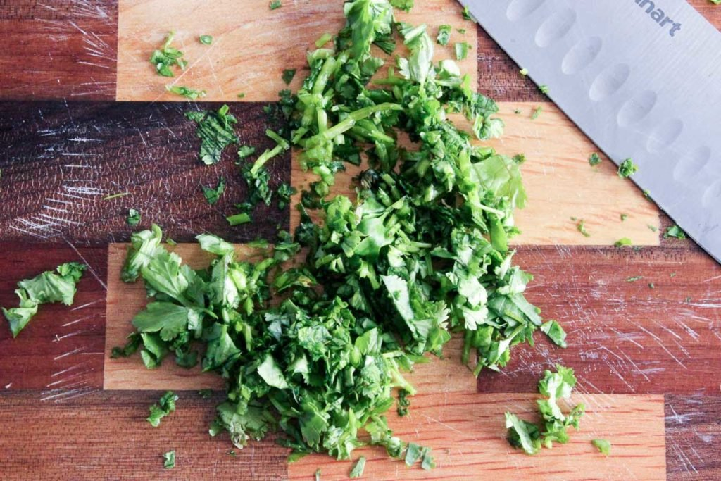 Chopped cilantro on wooden cutting board