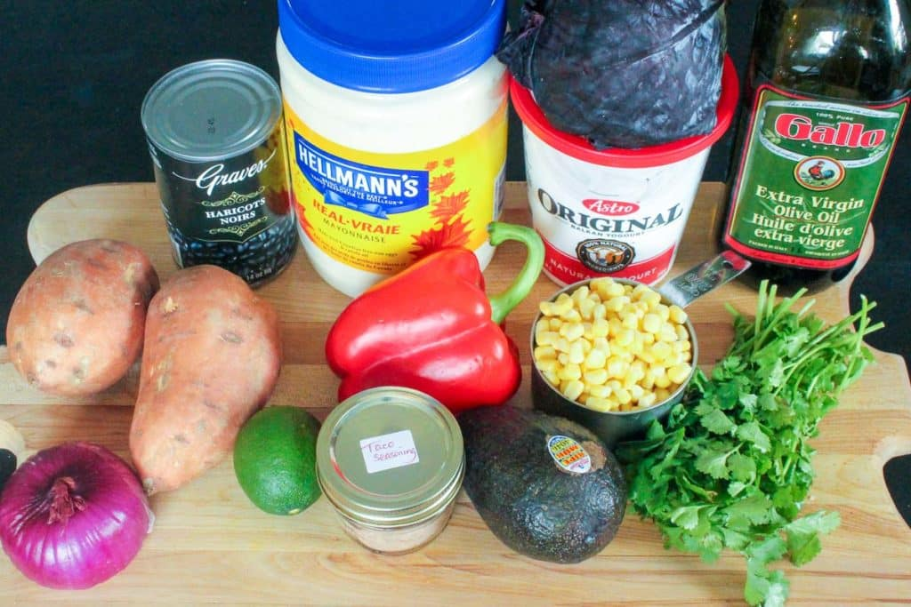 Wooden cutting board holindg sweet potatoes, black beans, avocado, corn, cilantro, red onion, lime, taco seasoning, red pepper, mayo and yogurt