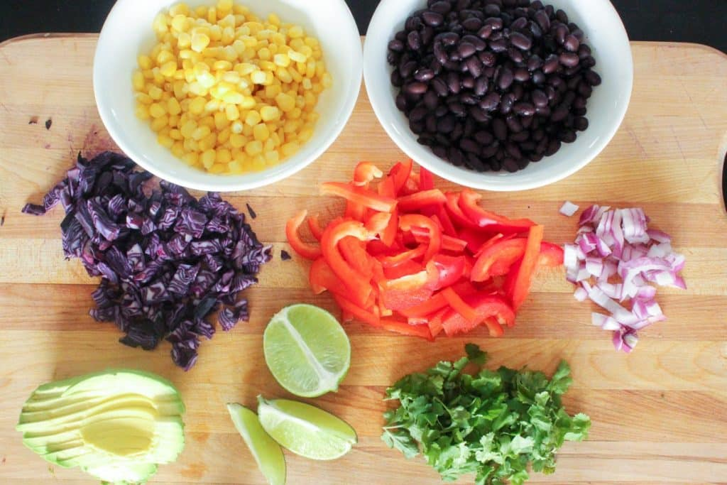 Wooden cutting board topped with bowl of corn, bowl of black beans, chopped red cabbage, chopped red pepper, diced red onion, sliced avocado, wedges of lime and cilantro leaves