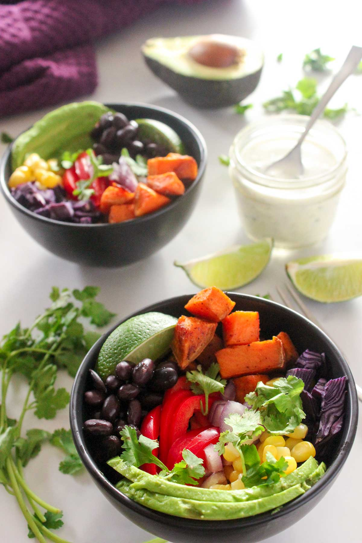 Black bowls with avocado, black beans, corn, red pepper, cilantro and sweet potatoes
