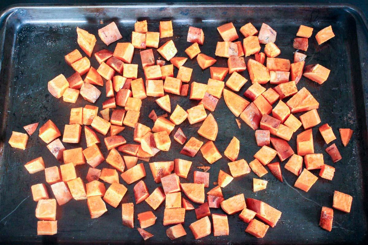 Sheet pan of cubed sweet potatoes with taco seasoning