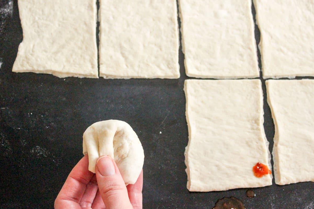 Square of stuffed pizza dough folded into ball
