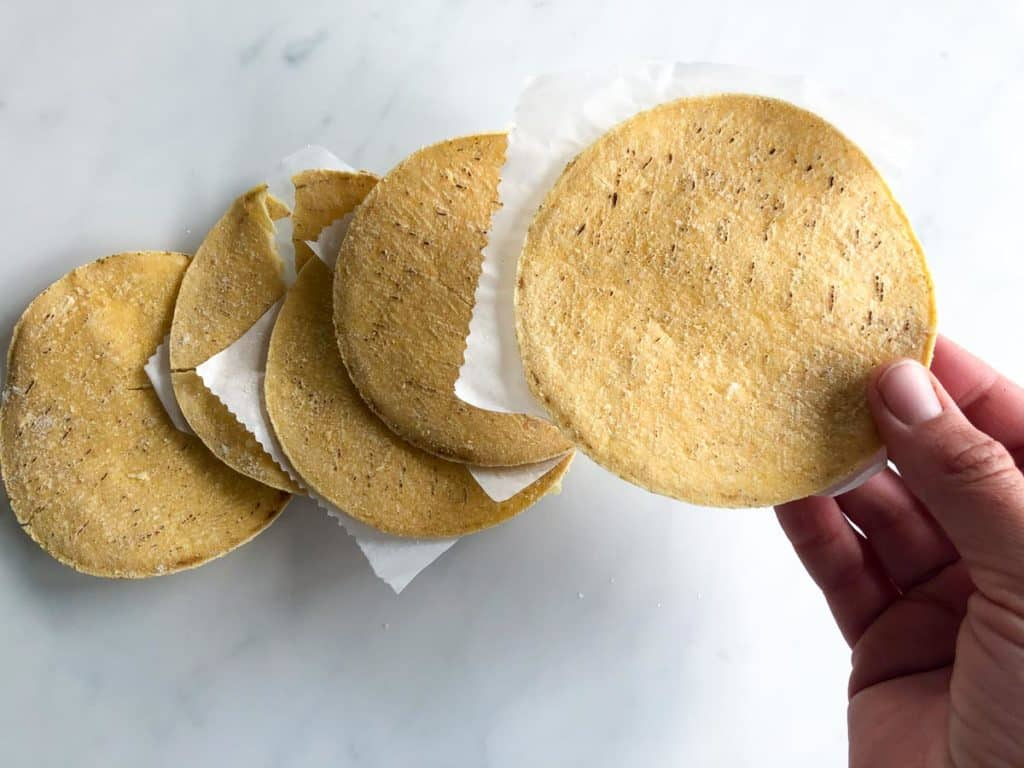 Corn tortillas after defrosting when layered with parchment paper