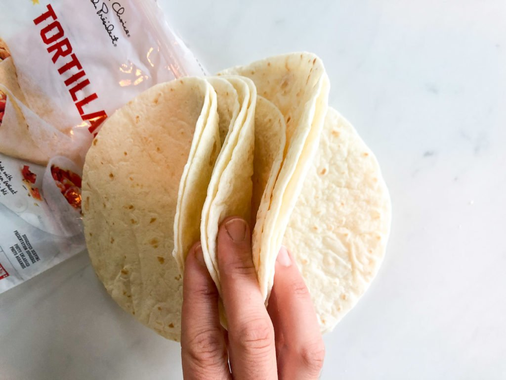 Stack of flour tortillas held up by hand