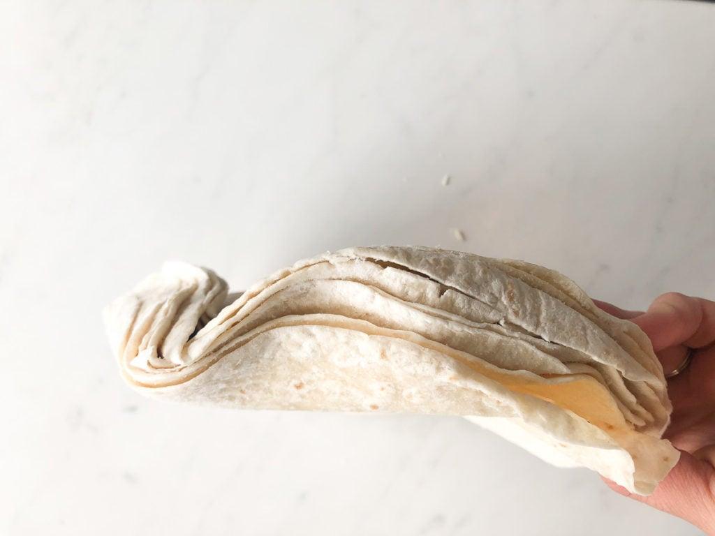 Hand holding stack of bent flour tortillas