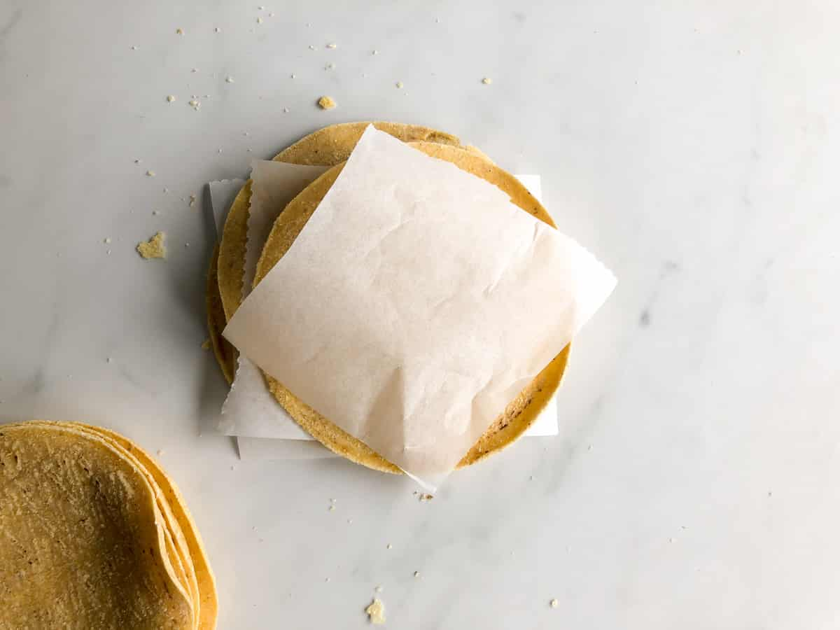 Stack of corn tortillas layered with parchment paper between them