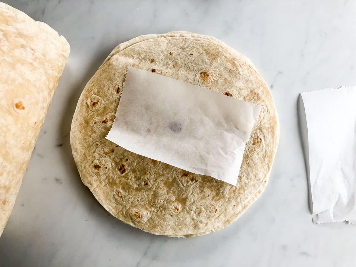 Stack of flour tortillas with a piece of parchment paper on top