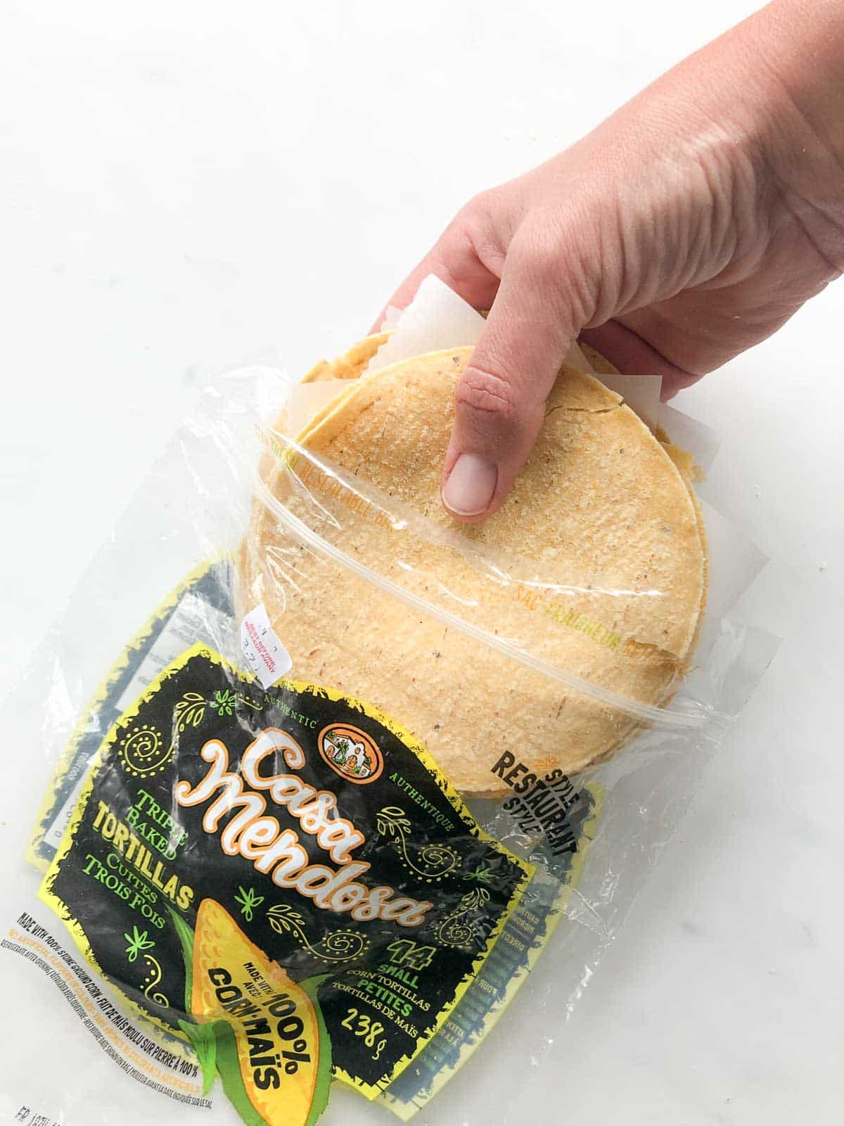 Bag of corn tortillas with a hand removing the tortillas