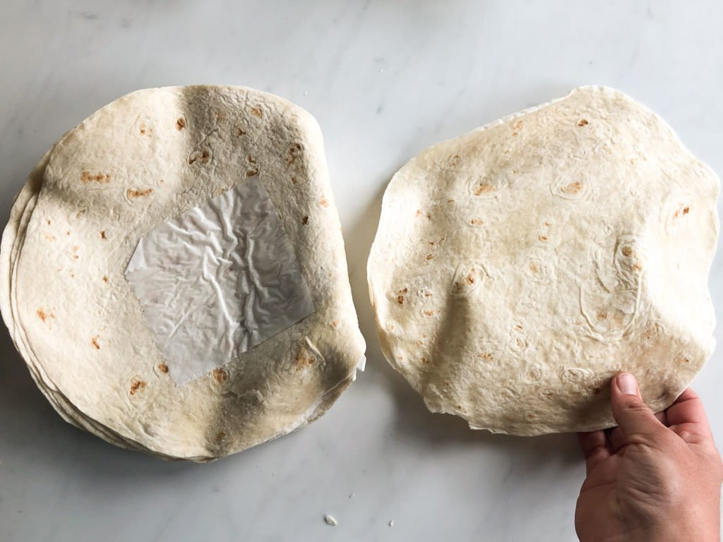 Stack of frozen flour tortilla wraps with one peeled off top