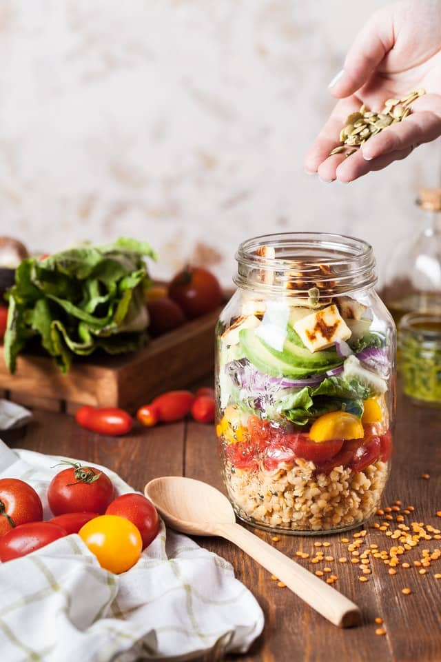 Mason jar full of vegetables for salad, with hand pouring pumpkin seeds into it.