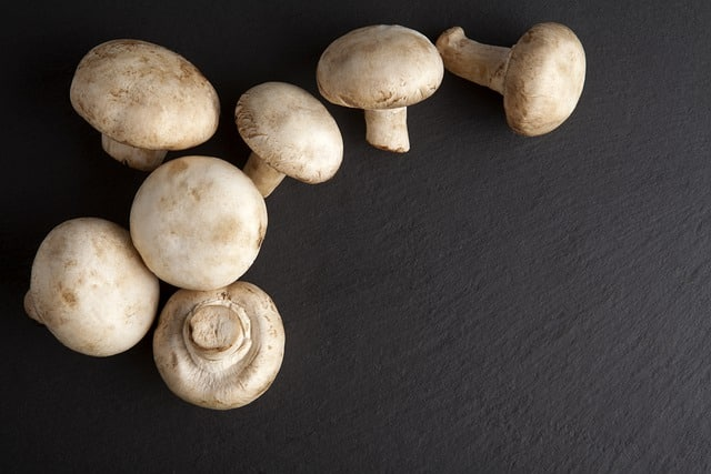 Seven clean, whole white button mushrooms on a black background.